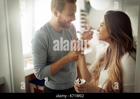 Paar Spaß zu haben und zu Hause lacht während Eis essen Stockfoto