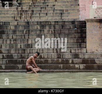 Varanasi, Indien - 12 Jul, 2015. Ein junger Mann baden auf dem Ganges in Varanasi, Indien. Varanasi, auch als Kashi - Stockfoto
