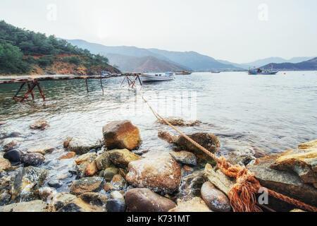 Boote in der Nähe der Pier gebrochen, indem in einer ruhigen ruhigen blauen Meer Wasser - Stockfoto
