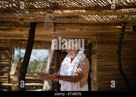 Lächelnde Menschen Waschen der Hände von der Dusche in der Hütte während der Safari Ferienhäuser - Stockfoto