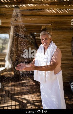 Porträt des Menschen Waschen der Hände von der Dusche in der Hütte während der Safari Ferienhäuser - Stockfoto