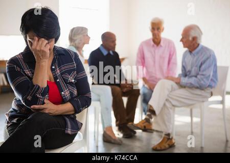 Sorgen ältere Frau mit Freunden im Hintergrund in der Kunst Klasse - Stockfoto