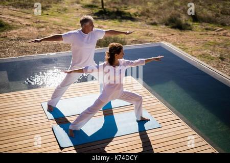 Paar Üben Yoga auf am Pool an einem sonnigen Tag - Stockfoto