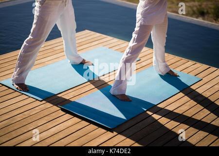 Untere Partie der Paar Üben Yoga auf am Pool an einem sonnigen Tag - Stockfoto