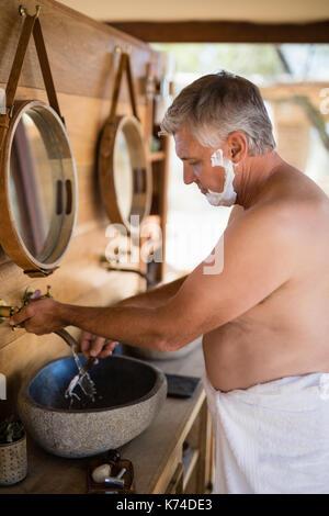 Man Rasiermesser Waschen im Cottage während Safari Ferienhäuser - Stockfoto