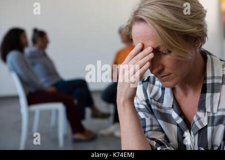 Frau mit Kopf in der Hand, während Freunde diskutieren im Hintergrund Kunst Klasse - Stockfoto