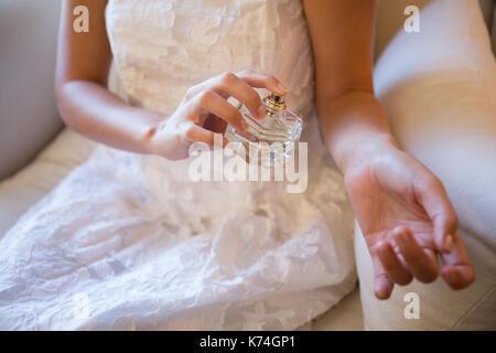 Mittelteil der Braut spritzen Parfüm auf Hand, während zu Hause sitzen - Stockfoto