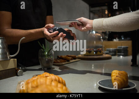 Frau Zahlung Rechnung durch das Smartphone mit der NFC-Technologie in Restaurant - Stockfoto
