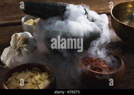 Verschiedene Arten von Gewürzen in Schale auf Holztisch - Stockfoto