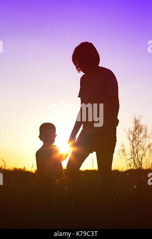 Silhouette einer Frau mit ihrem Kind bei Sonnenuntergang. - Stockfoto