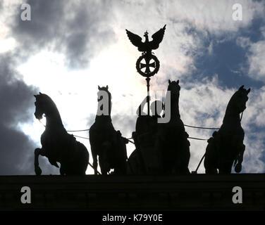 Hintergrundbeleuchtung der vier Pferde mit dem Wagen und der Göttin sind das Wahrzeichen der Stadt Berlin in Deutschland. - Stockfoto
