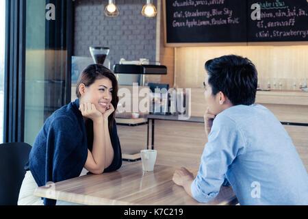 Partnersuche in einem Cafe. Schöne asiatische Liebhaber Paar sitzt in einem Café in Kaffee und Unterhaltung genießen. - Stockfoto