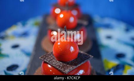 Drei rote Kuchen mit Keksen und Schokolade. Lecker Kuchen auf roten Hintergrund dunkel blau - Stockfoto