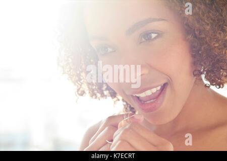 Portrait von Mitte der erwachsenen Frau Zähne flossing. - Stockfoto
