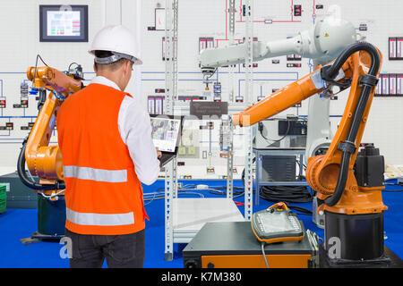 Techniker installieren und testen der Industrie Roboter in der Fertigung im Werk - Stockfoto