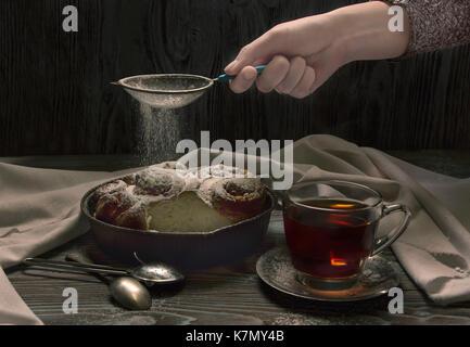 Frau giesst Zucker Pulver auf der Torte. Dark Photo - Stockfoto