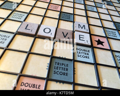 """Die Worte """"Liebe mich"""" heraus auf einem Scrabble Spiel Brett geschrieben - Stockfoto"""