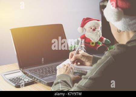 Frauen tragen santa claus red hat schriftlich auf dem Notebook mit Laptop und Santa Claus Doll auf Weihnachten. - Stockfoto