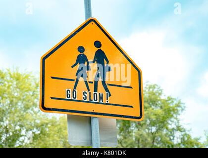 Schule crossing Schild mit blauem Himmel und gehen Sie langsam Schriftzug - Stockfoto