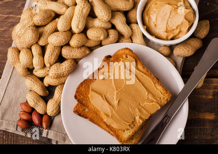 Teil der Peanut butter Sandwiches mit Erdnüssen in Shel über schwarzen Holz- Hintergrund - Stockfoto