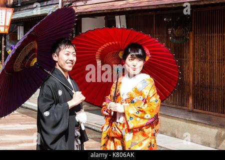 Lächelndes Paar, in 20s, das Tragen von Kimonos und Holding Sonnenschirme, stehend in der berühmten Straße in Higashi - Stockfoto