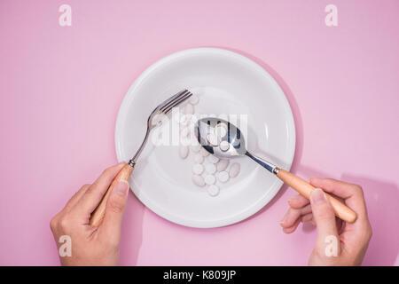 Draufsicht auf die Hände des Mannes am Esstisch mit Messer und Gabel vor Gericht mit Pillen über rosa Hintergrund. - Stockfoto