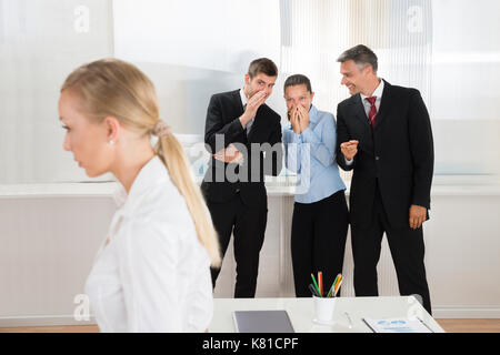Gruppe von Happy Geschäftsleute flüsternd über Frau im Büro - Stockfoto