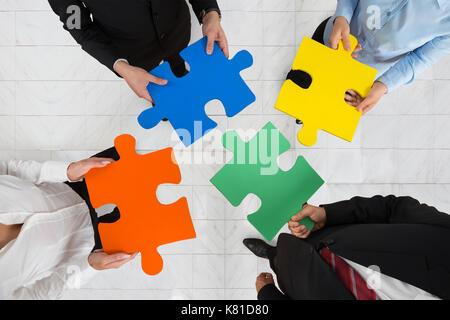 Hohe Betrachtungswinkel aus Geschäftsleuten Team Holding bunte Puzzleteile in den Händen - Stockfoto