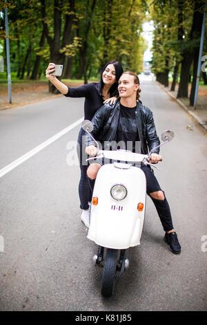 Eine junge fröhliche Paar Touristen auf einem Oldtimer Roller in der Stadt, der grauhaariger Mann einen selfie mit - Stockfoto