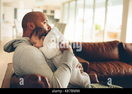 Little Boy auf der Brust seines Vaters. Junger Mann sein baby boy Holding in die Arme und sitzt auf einem Sofa zu - Stockfoto