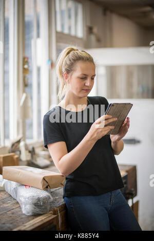Frau mit blonden Haaren stehen in einem Workshop mit einem digitalen Tablet, verpackte Pakete auf einen Tisch. - Stockfoto