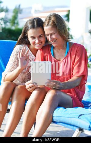 Mutter und Tochter bleiben Sie in Kontakt mit Freunden und Familie mit Hilfe eines digitalen Tablet während des - Stockfoto