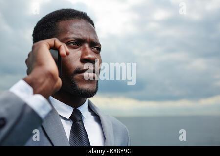 Zeitform Geschäftsmann mit Smartphone ruft im Freien bei stürmischem Wetter - Stockfoto