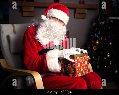 Santa Claus mit einem Geschenk Box in Home - Stockfoto