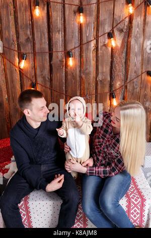 Glückliche Familie an Weihnachten. Die Eltern und das Baby sitzen. Wand aus Holzbohlen und Garland - Stockfoto