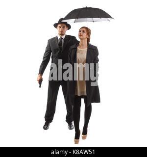 Eine Dame, die in förmlichen tragen mit ihrem Bodyguard Holding einen Regenschirm - Stockfoto