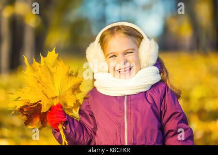 Glückliches kleine Mädchen in Ohrenklappen mit Herbst Blätter - Stockfoto