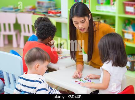 Asiatische Frau Lehrer Lehre gemischten Rennen Kinder Lesung buchen Sie im Klassenzimmer, Kindergarten Vorschule Konzept.