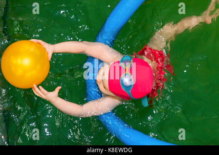 Blick von oben auf ein Kleinkind Mädchen schwimmen lernen mit pool Nudel in einem Meerwasserpool - Stockfoto