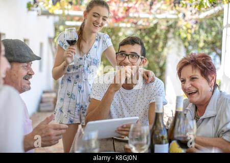 Familie mit Mittagessen im Freien unter Grapevine trellis - Stockfoto