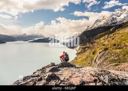 Männliche Wanderer hockend über graue See und Gletscher, Torres del Paine Nationalpark, Chile zu suchen - Stockfoto