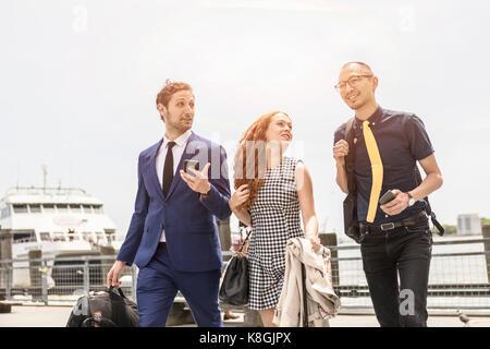 Geschäftsleute und Frau gehen und sprechen über die Waterfront, New York, USA - Stockfoto