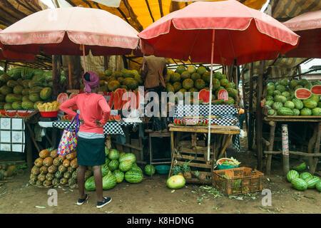 Frau steht an Wassermelone warten Stall als Eigentümer auf Hocker in der Rückseite der Shop steht, Kenia - Stockfoto