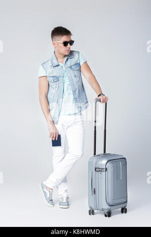 Junger Mann im blauen Hemd mit Koffer - Stockfoto