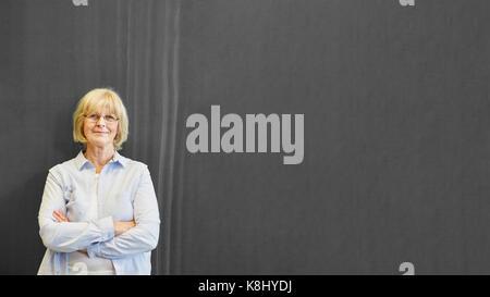 Die Frau als Lehrerin vor dem Schwarzen Brett in der Schule - Stockfoto