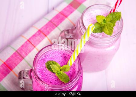 Berry Milchshake oder Smoothie mit Zutaten und Minze. Gesundes Getränk in Mason jar. - Stockfoto