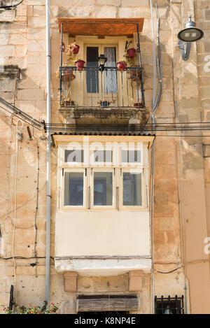 Ein traditionelles Gebäude aus Stein in Malta mit einem maltesischen Balkon - Stockfoto