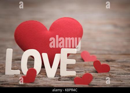 Red Kissen Herzform und liebe Wort auf Holzuntergrund mit Raum zu schreiben. Valentine Konzept, Vintage Tone, AF - Stockfoto