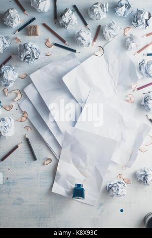 Leeres Papier auf einer hölzernen Hintergrund mit Tintenfass und zerstreute zerknittertes Papier Kugeln, Bleistifte, - Stockfoto