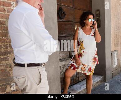 Stilvolle italienische Frau Gespräch am Handy auf der Straße, Sienna. - Stockfoto